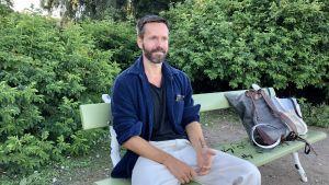 Koreografen Alexander Ekman sitter på en bänk.