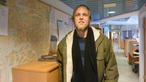 Vit man med ljust hår och skägg står inomhus med jacka och halsduk framför en karta på en vägg.