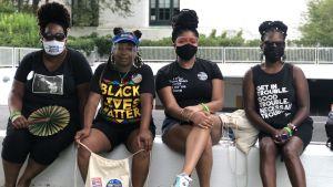 Tre svartklädda kvinnor med munskydd sitter på en mur.