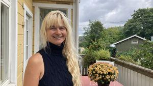 En kvinna med långt, blont lockigt hår står vänd mot kameran och ler. Hon står på verandan av ett gult trähus, och bakom henne syns buskar och träd.