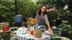 Ulla Erjala står och diskar vid sitt trädgårdsbord i Kuppis koloniträdgård i Åbo