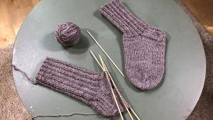 Sukkaneuleprojekti ja valmis sukka pöydälla