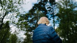 Äldre i blå jacka utomhus omgiven av trädkronor. Sirkka Kurkela i Esbo i maj 2020.
