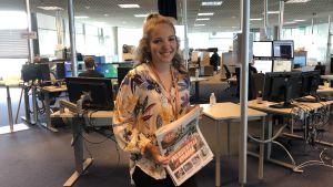 En ung leende kvinna vid en nyhetsredaktion.