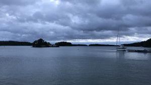 Vy från Gumbostrand mot skärgården. Till vänster syns en segelbåt förtöjd vid en brygga.
