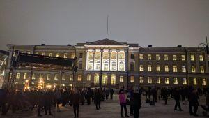 Helsingin yliopiston päärakennus iltahämärissä, etualalla suuri yleisöjoukko.