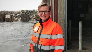Kvinna i orange jacka framör en hög med sopor.