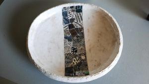 Ett vitt keramikfat med blågröna detaljer i mitten.