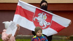 En mamma och två barn demonsterar för den belarusiska oppositionen. Mamma bär en röd-vit flagga, barnet håller upp en teckning som föreställer en riddare på en vit häst.