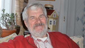 En man med grått hår och grått skägg sitter i en soffa. HAn ler och ser ganska nöjd ut.Porträttbild.