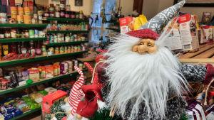 Till vänster syns en butikshylla med olika produkter på, till höger närmare i bild en jultomte.