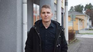 En ung man i kort ljudbrunt hår och svart skjorta med svart ytterkappa på.