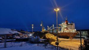 Ett fartyg står vid en kaj i en hamn. Det är vinter och mörkt.