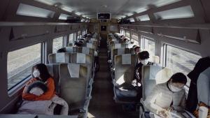Passagerare i ett snabbtåg i Sydkorea sitter med munskydd över ansiktet. En person per säte gäller i Sydkorea under den tredje vågen av coronapandemin.