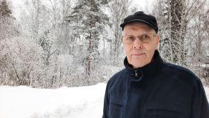 Ahti Lappi, i svarta vinterkläder med snöklädda träd i bakgrunden, småler.