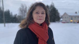 Kvinna med ytterrock och roströd halsduk står ute i vintrigt landskap. Tittar leende in i kameran.