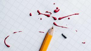 kuvituskuva katkennut lyijykynä ja punaista väriä ruutuvihkon päällä