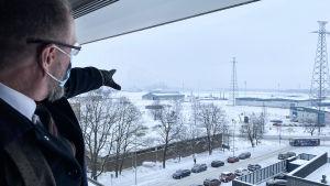 Man pekar ut genom fönstret mot hamnområde.