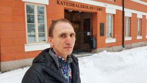 Herman Norrgrann, en man med svart dunjacka, står framför en orangebrun byggnad.