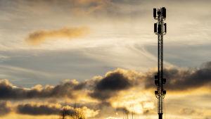 En basstation för bredband mot en gul och molnig himmel.