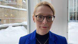 Ulrika Krook, jursit och universitetslärare poserar i en blå kavaj vid Svenska social- och kommunalhögskolan. Det är vinter utanför fönstren, hon ser bestämd ut.