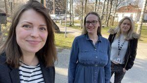 Tre kvinnor poserar utomhus