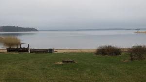 Vy från strand över spegelblankt hav. Disig morgon i mitten av april.