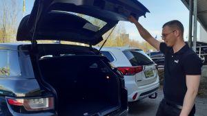 BIlförsäljare öppnar bakluckan på en bil och tittar in