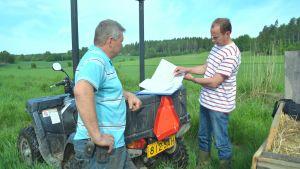 Ville Wahteristo visar ritningarna av våtmarken åt jordbrukare Anders Wasström.