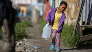 Pojke bär vatten till sitt hem.