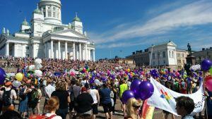 Senatstorget vimlar av pridedeltagare pch ballonger i olika färger under Helsingfors pride 2016.