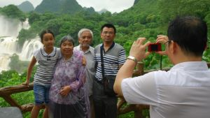 Shi fotograferar en jordbrukarfamilj som turistar i sitt hemlandskap. Den inhemska turismen blomstrar då allt fler kineser har råd att besöka sevärda platser. Själv tog Shi sina fotografier med en iPad.