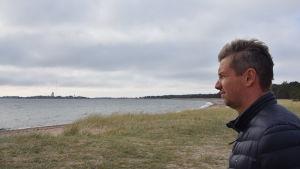 Man klädd i mörkblå jacka blickar ut över en strand.