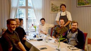 En bild på sju män som har startat en förening för köksmästare. De sitter runt ett bord och ler mot kameran. I bakgrunden finns ett fönster.