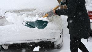 person med snöskyffel invid bil