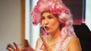 Noora Määttä päällään vaalea iltapuku ja pinkki peruukki La Kalan esityksessä.