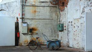 En blå cykel framför en vägg inne i Stora smedjan i Bilnäs bruk.