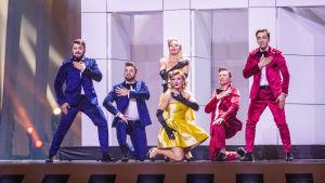två kvinnor och fyra män i färgglada kläder