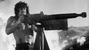 Sylvester Stallone som Rambo skjuter med tungt automatvapen.