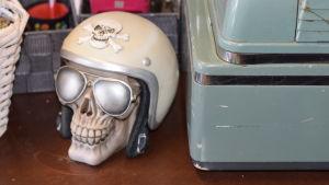 Ett prydnadsföremål som föreställer en dödsskalle med motorcykelhjälm. Finns på ett bord.