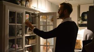 Jan- Christian Forsman sätter matvaror in i vita köksskåp