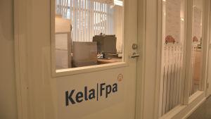 En glasdörr med texten Kela/Fpa. Innanför syns ett kontor.