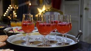 En bricka med vinglas fyllda med tranbärsdryck.