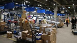 Inne i en logistikcentral med stora mängder paket framför rullband.