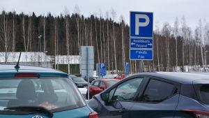 Bilar på en parkeringsplats. På en skylt står det att platserna närmast kameran är till för personal.
