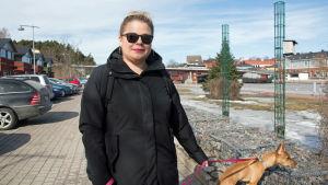 En kvinna med en hund vid Borgå å.