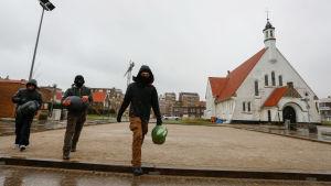 Tre migranter utanför kyrkan i Zeebrugge.