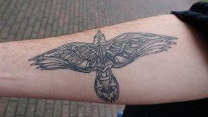 Bild på en arm som har en tatuering av en fågel