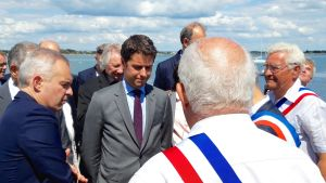 statssekreteraren Gabriel Attal som tar emot presenter av öns lokalpolitiker. Till vänster  syns miljöminister François de Rugy.