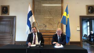 Antti Kaikkonen och Peter Hultqvist sitter vid ett bord med Finlands och Sveriges flaggor i bakgrunden.